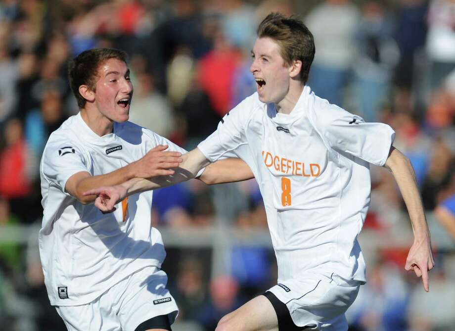 Ridgefield's Daniel Standish (8) celebrates his goal with a teammate in Ridgefield's 1-1 tie with Glastonbury in the CIAC Class LL high school boys soccer championship game at Municipal Stadium in Waterbury, Conn. on Saturday, Nov. 16, 2013. Photo: Tyler Sizemore / The News-Times