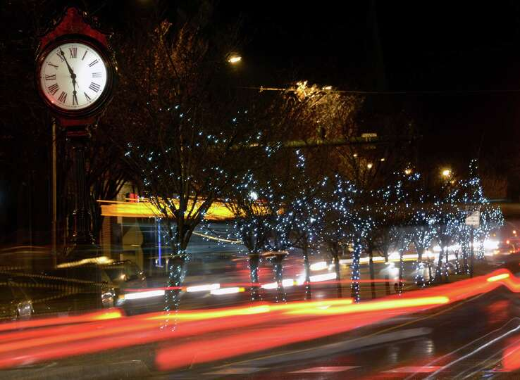 Traffic passes by trees, decorated with festive holiday lights, along Main Street in Danbury, Conn.