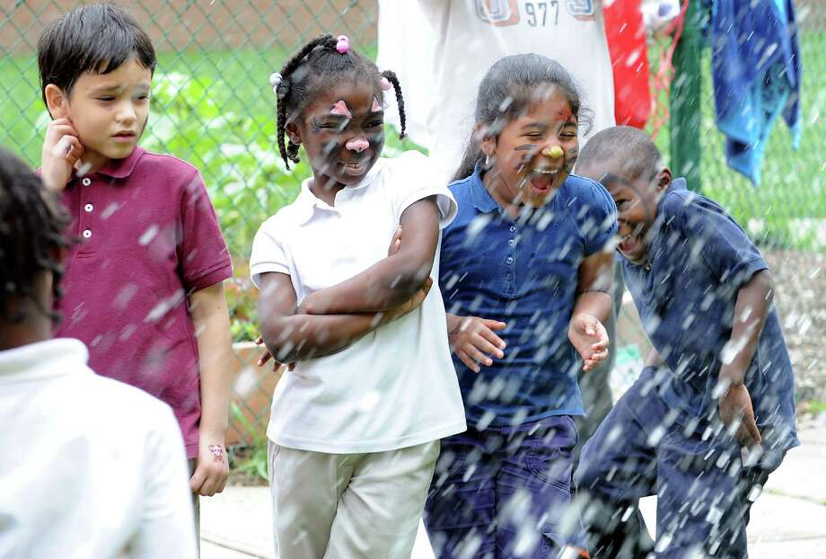 Wilbur Cross School kindergarten students David Colon, Ariana Mack, Eva Iyavaca and Xavier Mann get splashed as teacher Lore Webster drops into the dunk tank at the school's June Jamboree on Friday, June 14, 2013. The jamboree is a way to reward the Bridgeport, Conn. students. Photo: Cathy Zuraw / Connecticut Post