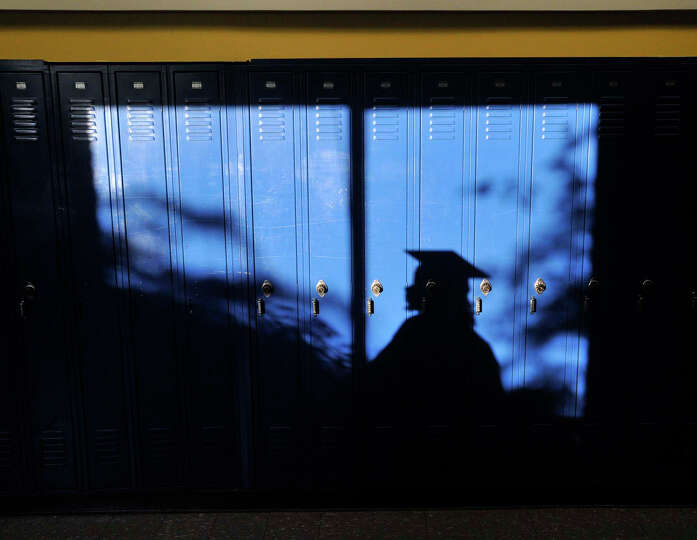 A graduate passes lockers in the hallway before the adult and continuing education commencement cere