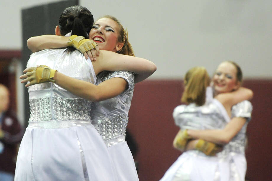 Jamie Demers, left facing forward, and Molly Dolman, far right, hug their teammates at the conclusion of the Bethel High School varsity winter guard routine at the Bethel Winterguard Home Show at Bethel High School in Bethel, Conn. Saturday, Feb. 23, 2013. The music briefly stopped during their routine, but the team held it together and completed its performance anyway. Photo: Tyler Sizemore / The News-Times
