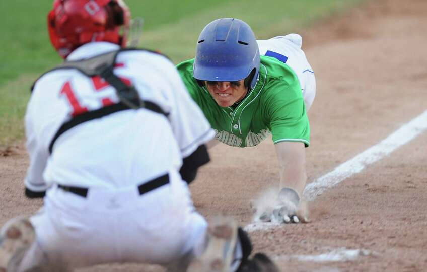 Newtown's Steven Conway slides into home as Pomperaug catcher Steve Harrison tags him out during New