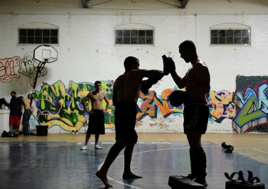 Nicolas Milligan, right, of Danbury, assists club trainer Santos Escribano, Jr. with a conditioning exercise at the Harambee Center For Youth boxing club in Danbury, Conn. on Wednesday, June 5, 2013. Photo: Tyler Sizemore / The News-Times