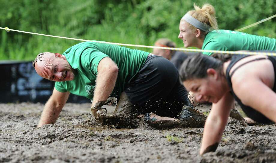Brad Eggleston, of Newtown, crawls through the mud pit in the 2013 Newtown Mad Dash at the Fairfield Hills campus in Newtown, Conn. on Saturday, June 8, 2013.  The second annual adventure run featured nine obstacles, including a climbing wall, water cannon balance beam, tire run and a mud pit.  Over 400 runners participated between the two divisions with Newtown's Kevin Hoyt placing first in the advanced division. Photo: Tyler Sizemore / The News-Times