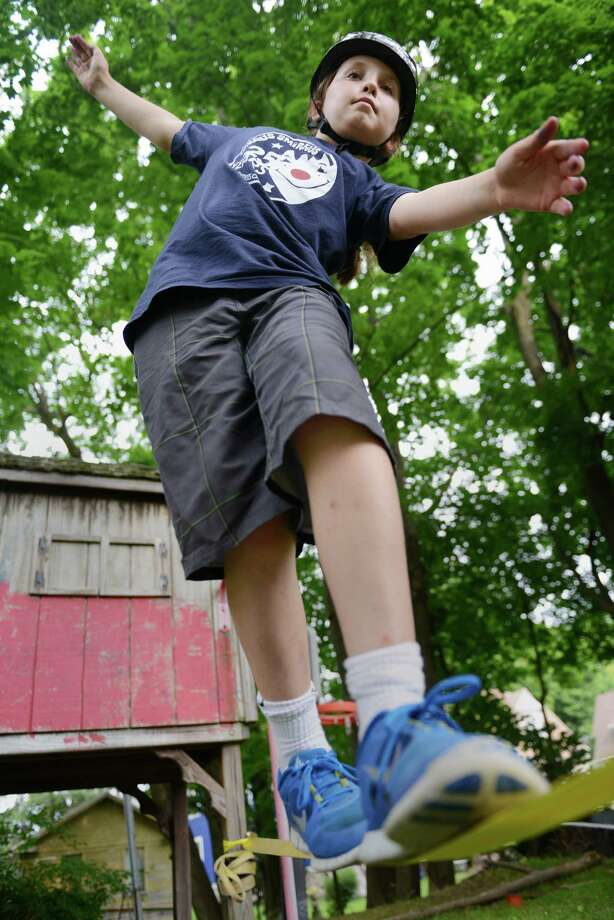 Elijah Crehan, 11, keeps his balance on a slack line tied to trees outside his home in Danbury, Conn. on Thursday, June 27, 2013.  Crehan does many other circus tricks including juggling and unicycle, but recently took up the slack line. Photo: Tyler Sizemore / The News-Times