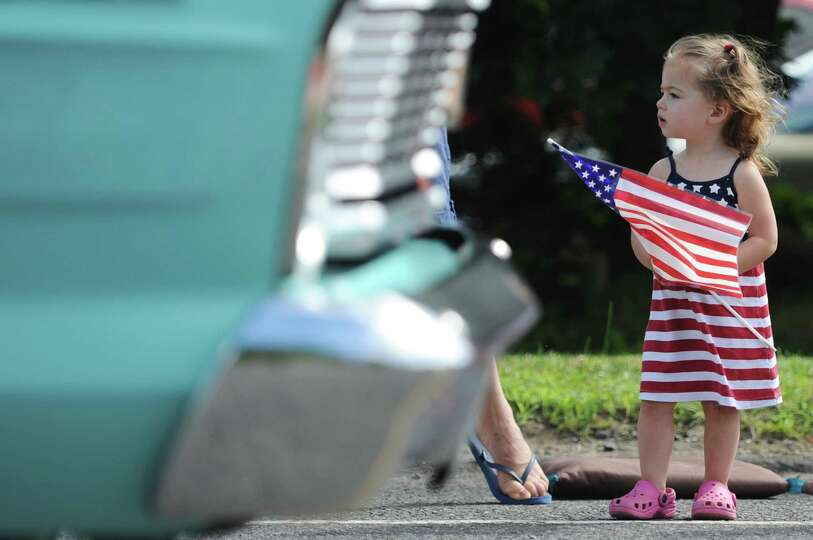 A child watches as a classic car drives past at the Annual Independence Day Parade in New Fairfield,