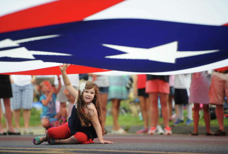 "Emily Godbout, 5, of Sandy Hook, helps to hold up a giant American flag at the start of the 52nd Annual Newtown Labor Day Parade in Newtown, Conn. on Monday, Sept. 2, 2013.  About 100 floats and groups participated in the parade, themed ""We are Newtown - marching strong."" Photo: Tyler Sizemore / The News-Times"