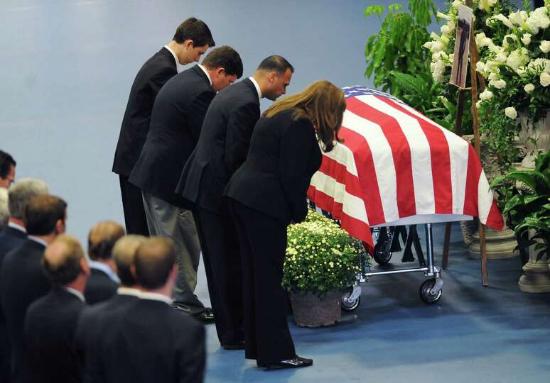 Florists and funeral directors bow their heads in front of the casket of TJ Lobraico during funeral