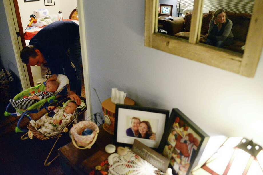 Rory Mason comforts his twin boys, Dylan, left, and Paul, as mother Janelle is reflected in the mirror in their home in Newtown, Conn. on Tuesday, Nov. 12, 2013.  Janelle and Rory had been trying to conceive and adopt for 15 years without any success.  However, Janelle's friend, Jennifer LaCava, agreed to be her surrogate to carry her children.  The surrogacy was successful and the boys are now 4 months old. Photo: Tyler Sizemore / The News-Times