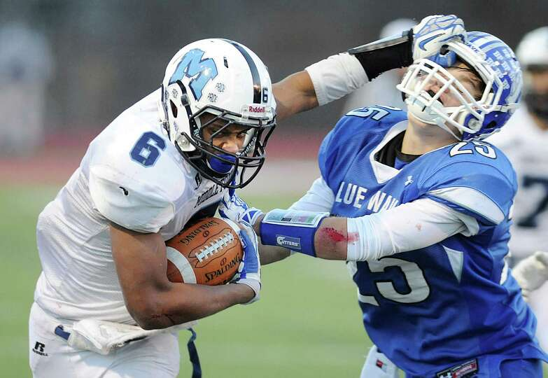 Middletown quarterback Dario Highsmith (6) stiff arms Darien defender John Reed (25) in Darien's 13-