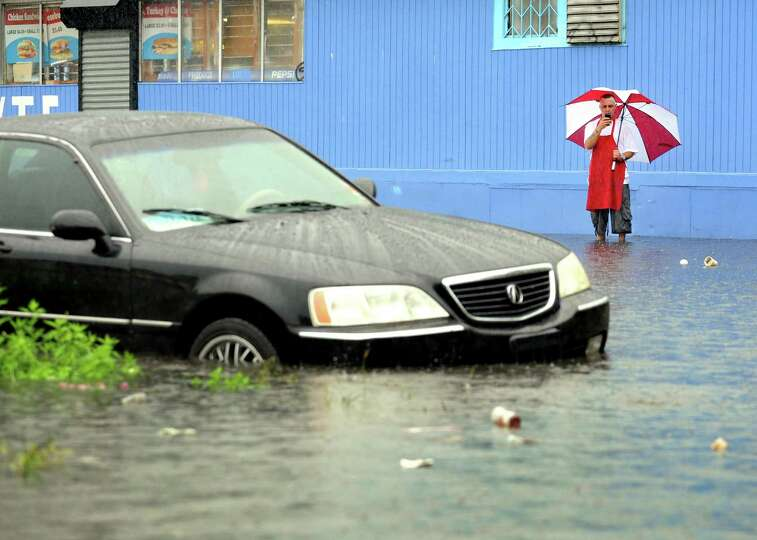 A man takes video of a car on a flooded Iranistan Avenue in Bridgeport. Conn. on Monday, June 3, 201
