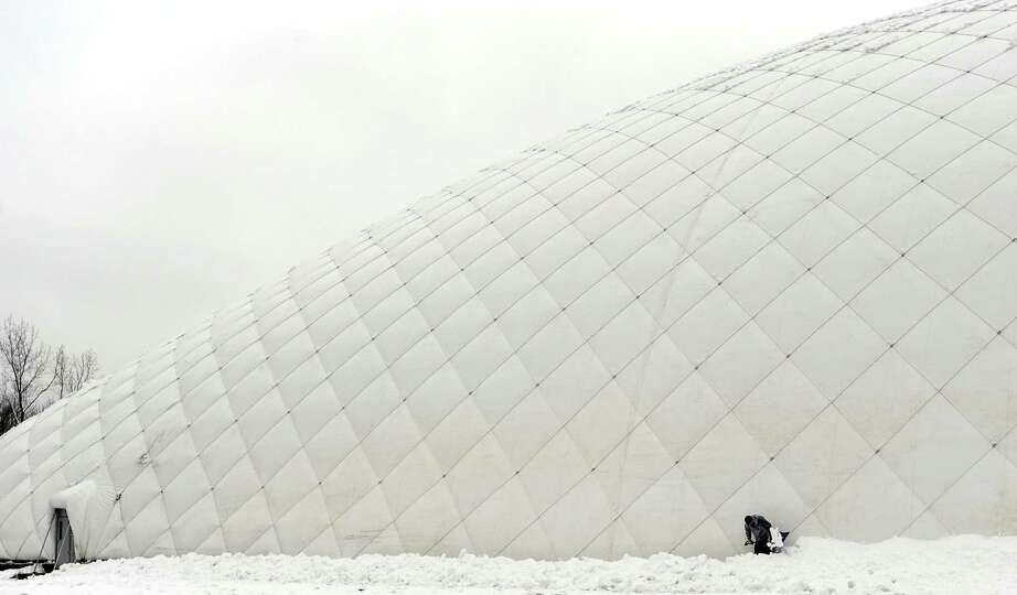 Rigo Guerra shovels along the base of the Danbury Sports Dome,a large air-supported complex under co