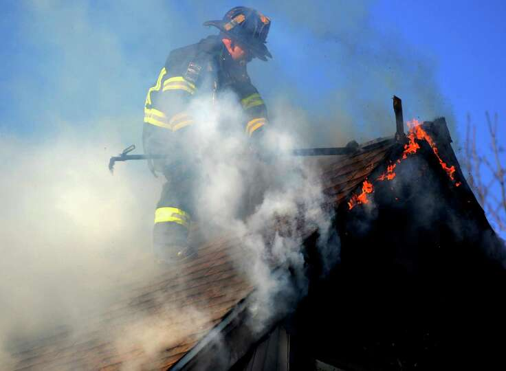 Bridgeport firefighter Mike Candela works high atop a roof to battle a blaze in a multi-family home