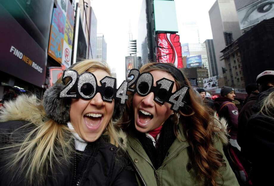 Veronica Boshen and Brittany Wells, of Allentown, Pa., pose for a photo with their 2014 glasses while waiting for the celebration to begin in Times Square on New Year's Eve, Tuesday, Dec. 31, 2013, in New York. Photo: Kathy Willens, AP / AP