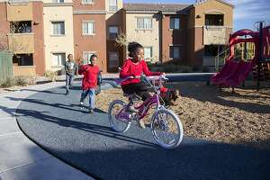 Jeraldine McNack (9) rides her new bike she received as an early Christmas gift as her brother, Justus (7), and a friend chase her through their southwest Las Vegas apartment complex on Tuesday, Dec. 24, 2013. (Alex Federowicz for San Francisco Chronicle)