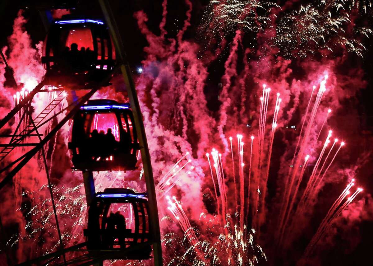 People ride a Ferris wheel as fireworks illuminate the sky over Edinburgh, Scotland, during New Year's eve celebrations late Tuesday Dec. 31, 2013. The celebrations this year are combined with marking the upcoming 2014 Commonwealth games. (AP Photo / David Cheskin, PA) UNITED KINGDOM OUT - NO SALES - NO ARCHIVES