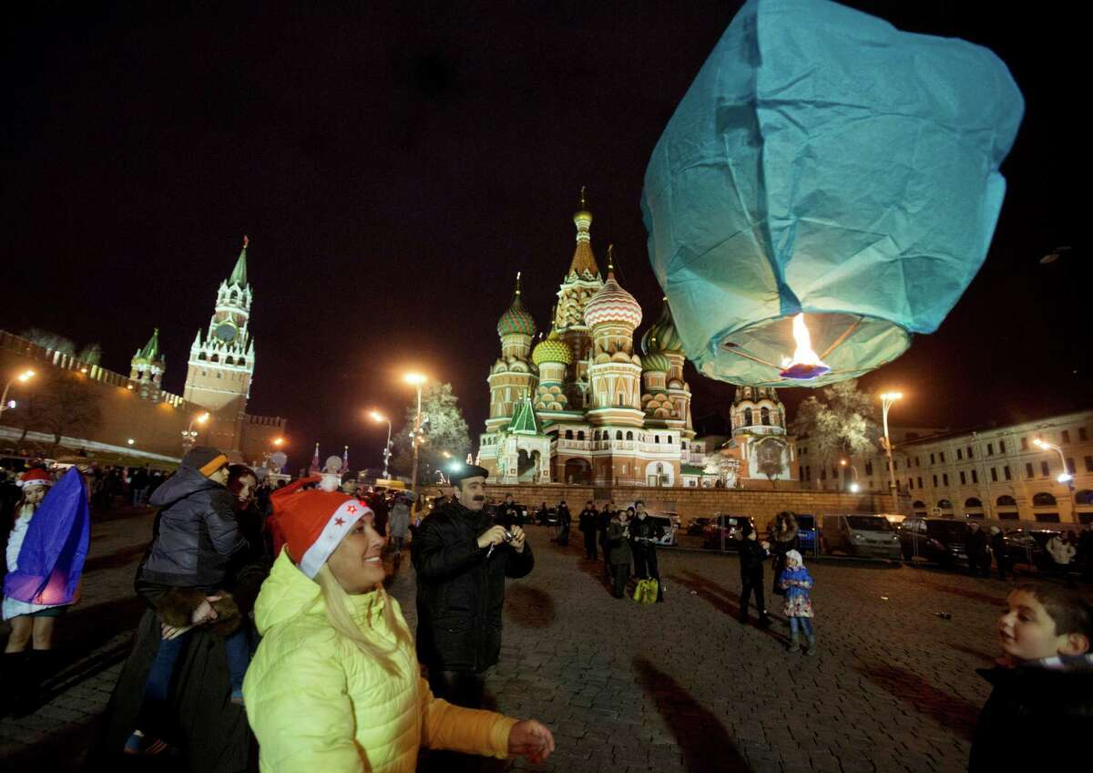 A woman launches a sky lantern during celebration for the New Year at the Red Square, in Moscow, Russia, early Wednesday, Jan. 1, 2014, with St. Basil Cathedral, centre right, and Kremlin's Spasskaya (Savior) Tower, left, are in the background. (AP Photo/Pavel Golovkin)