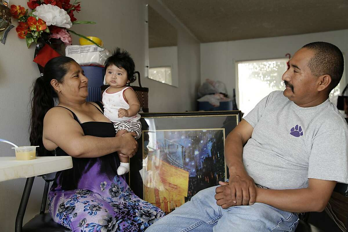 In this July 16, 2013 photo, Hilario Santiago Vasquez, right, looks on as his wife Josefina Hernandez Santiago holds the couple's 5-month-old daughter Esmeralda in Madera, Calif.A farmworker, Santiago Vasquez once followed the crops and slept under a bridge for lack of housing, but has since found permanent work and an apartment in California _ a state where Hispanics are more settled than anywhere else. (AP Photo/Gosia Wozniacka)