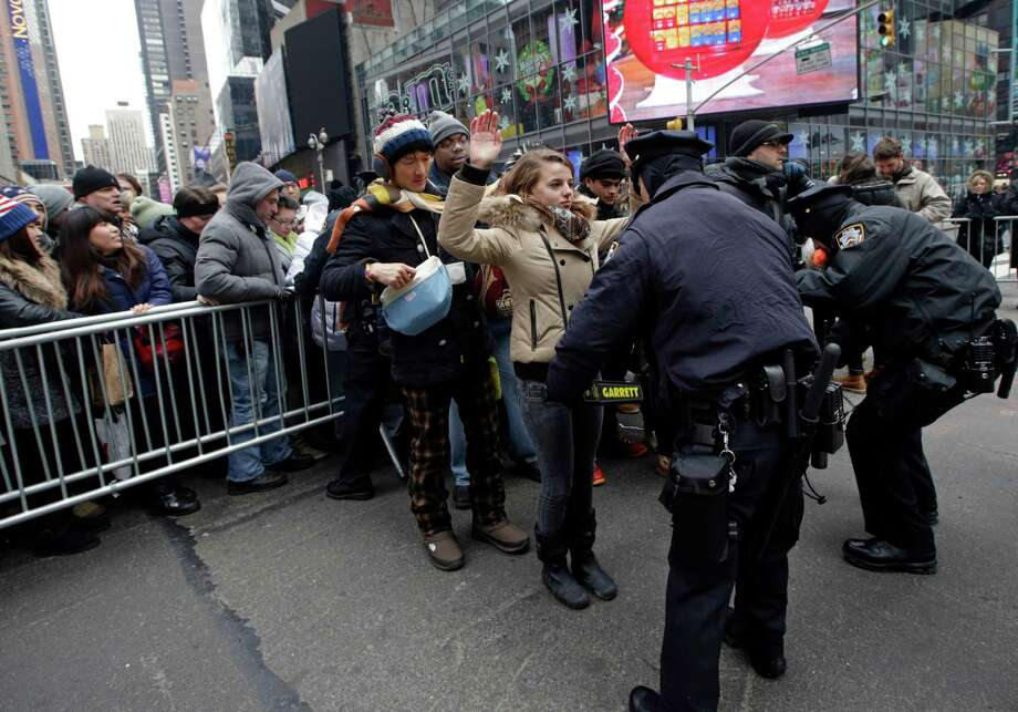 New York City police officers search people entering barricaded pens used to control crowds in Times Square in preparation for the ball drop on New Year's Eve, Tuesday, Dec. 31, 2013, in New York. Photo: Kathy Willens, AP / AP