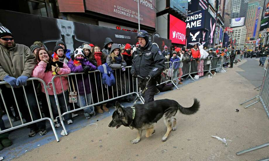 New York City K-9 officer Anderson guides his bomb-sniffing dog through a corridor as people gather in Times Square in preparation for the New Year's Eve ball drop, Tuesday, Dec. 31, 2013, in New York. Photo: Kathy Willens, AP / AP