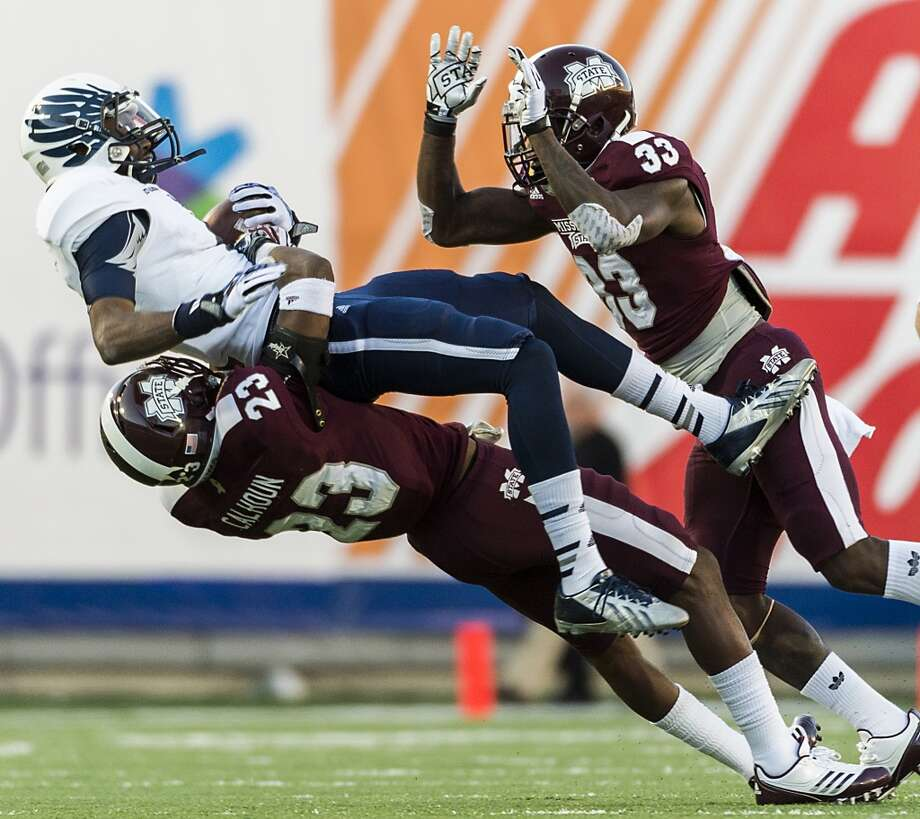 Rice wide receiver Dennis Parks (4) is slammed to the turf by Mississippi State defensive back Taveze Calhoun (23) during the first half. Photo: Smiley N. Pool, Houston Chronicle