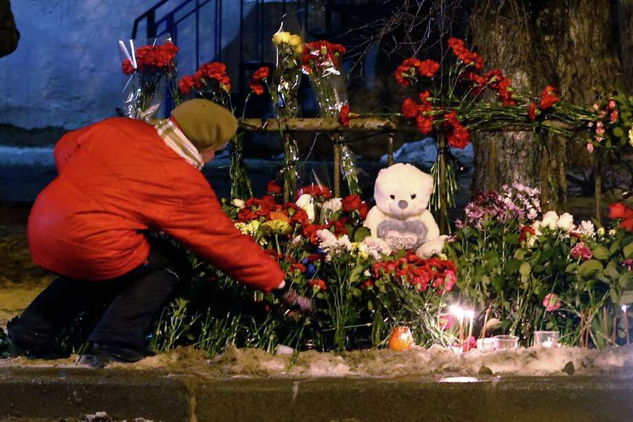 A woman adds to a makeshift memorial to victims of a suicide bombing in Volgograd, as Russia beefed up security Tuesday at train stations and other facilities. Photo: Denis Tyrin, STR / AP