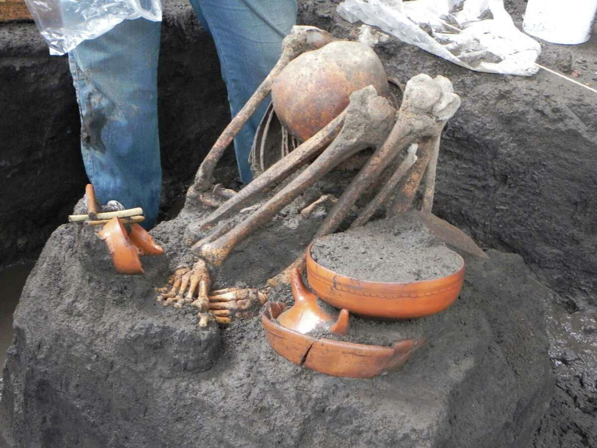 In this July 5, 2010 image released by Mexico's National Institute of Anthropology and History (INAH), the skeleton of an adult human lies next to an offering found during the excavations for the newest subway line in Mexico City. The institute says several offerings were found during the construction of the subway line performed between 2008 and 2011, but the finds were announced on Tuesday Dec. 31, 2013. (AP Photo/INAH)