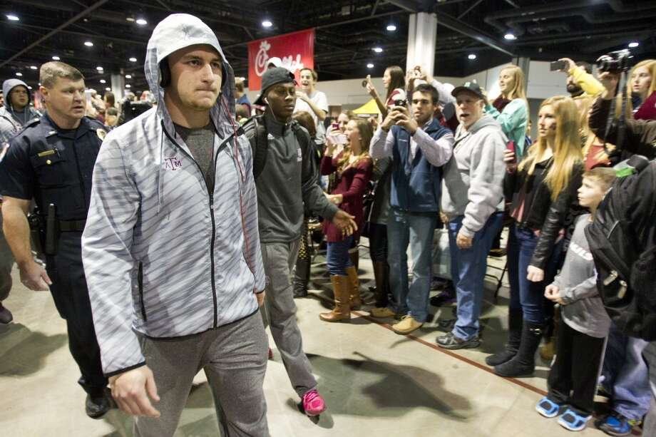 Texas A&M quarterback Johnny Manziel walks past a line of Aggie fans before facing Duke in the Chick-fil-A Bowl. Photo: Brett Coomer, Houston Chronicle