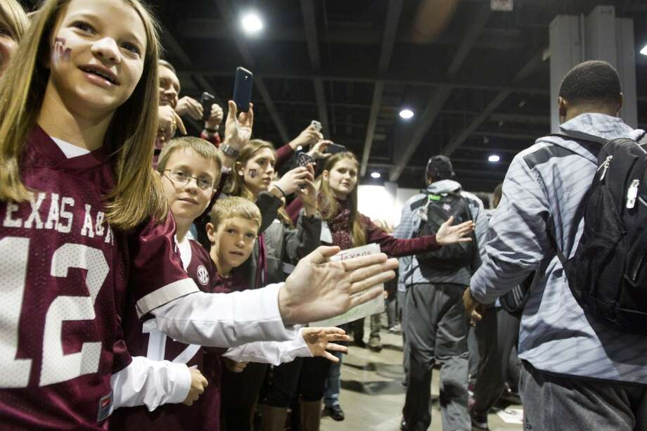 Texas A&M fans reach out for high-fives as the team walks past them before facing Duke in the Chick-fil-A Bowl. Photo: Brett Coomer, Houston Chronicle