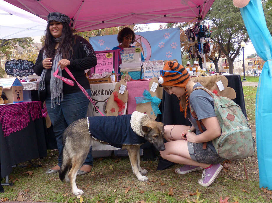 "Alexis Quiroga's dog, Sakari, greets customer Tia Kelly at the Holiday Market at Travis Park on Dec. 20. Quiroga makes all-natural ""human-grade"" treats for dogs and sells them at farmers markets. PAWsitively Sweet Bakery is her business. Photo: Billy Calzada / San Antonio Express-News / San Antonio Express-News"