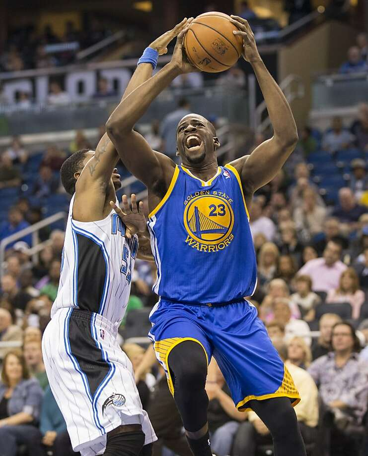 Golden State Warriors' Draymond Green, right,  takes the ball to the basket against Orlando Magic's E'Twaun Moore  during the second half of an NBA basketball game in Orlando, Fla., Tuesday, Dec. 31, 2013. (AP Photo/Willie J. Allen Jr.) Photo: Willie J. Allen,  Jr., Associated Press