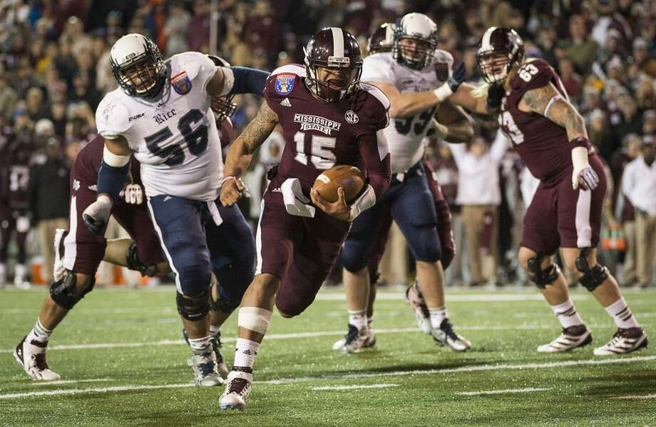 Mississippi State quarterback Dak Prescott (15) races past Rice defensive tackle Christian Covington (56) and defensive lineman Ross Winship (99) for an 11-yard touchdown run during the second half. Photo: Smiley N. Pool, Houston Chronicle
