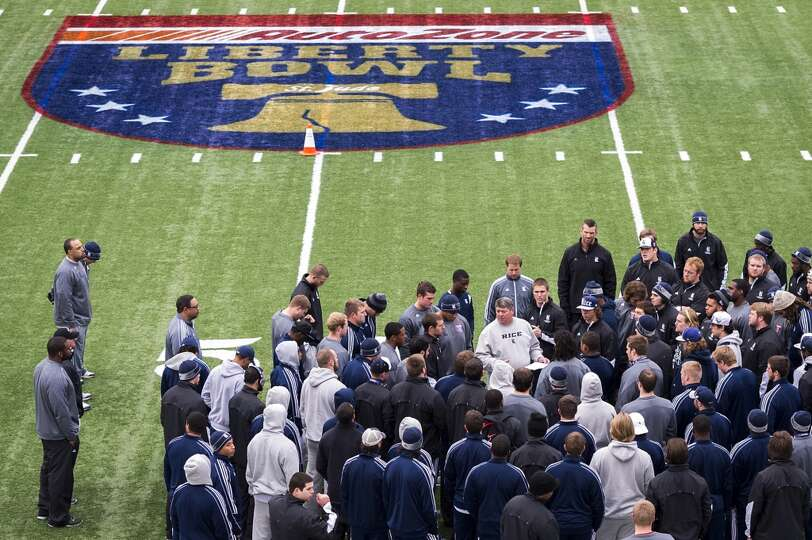 Rice players a coaches huddle around head coach David Bailiff during the team walkthrough before the