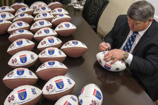 Rice head coach David Bailiff autographs footballs in advance of the 55th AutoZone Liberty Bowl, Monday, Dec. 30, 2013, in Memphis. Photo: Smiley N. Pool, Houston Chronicle