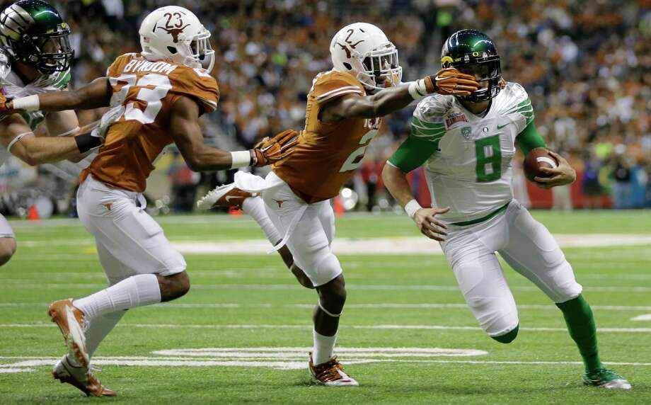 A Texas defense that was unable to stop Oregon's Marcus Mariota, right, in the Alamo Bowl will have to be vastly improved for the Longhorns in 2014. Photo: Eric Gay, STF / AP