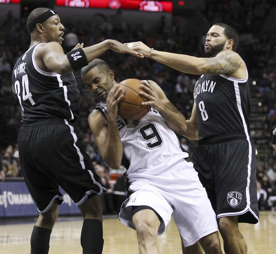 Spurs' Tony Parker (09) drives through the lane against Brooklyn Nets' Paul Pierce (34) and Deron Williams (08) in the first half at the AT&T Center on Tuesday, Dec. 31, 2013. (Kin Man Hui/San Antonio Express-News) Photo: San Antonio Express-News