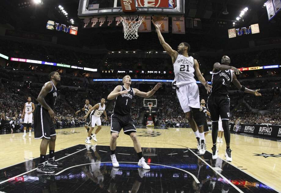 Spurs' Tim Duncan (21) lays up a shot against Brooklyn Nets' Kevin Garnett (02) and Mason Plumlee (01) in the second half at the AT&T Center on Tuesday, Dec. 31, 2013. Spurs win 113-92. (Kin Man Hui/San Antonio Express-News) Photo: San Antonio Express-News
