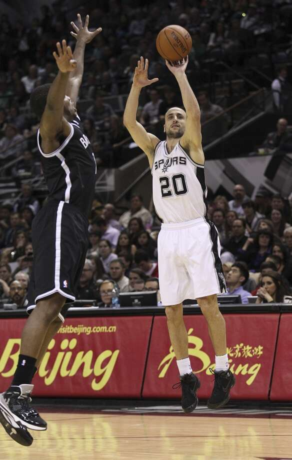 Spurs' Manu Ginobili (20) throws up a three-pointer against Brooklyn Nets' Alan Anderson (06) in the second half at the AT&T Center on Tuesday, Dec. 31, 2013. Spurs win 113-92. (Kin Man Hui/San Antonio Express-News) Photo: San Antonio Express-News