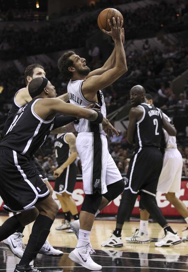 Spurs' Marco Belinelli (03) attempts a shot against Brooklyn Nets' Paul Pierce (34) in the second half at the AT&T Center on Tuesday, Dec. 31, 2013. Spurs win 113-92. (Kin Man Hui/San Antonio Express-News) Photo: San Antonio Express-News
