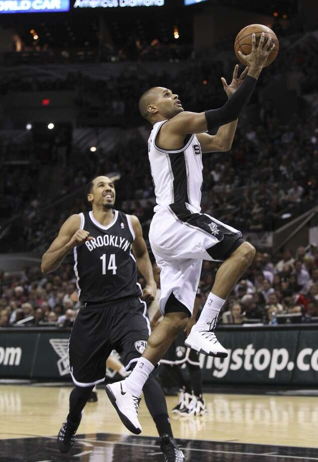 Spurs' Patty Mills (08) drives for a layup against Brooklyn Nets' Shaun Livingston (14) in the second half at the AT&T Center on Tuesday, Dec. 31, 2013. Spurs win 113-92. (Kin Man Hui/San Antonio Express-News) Photo: San Antonio Express-News