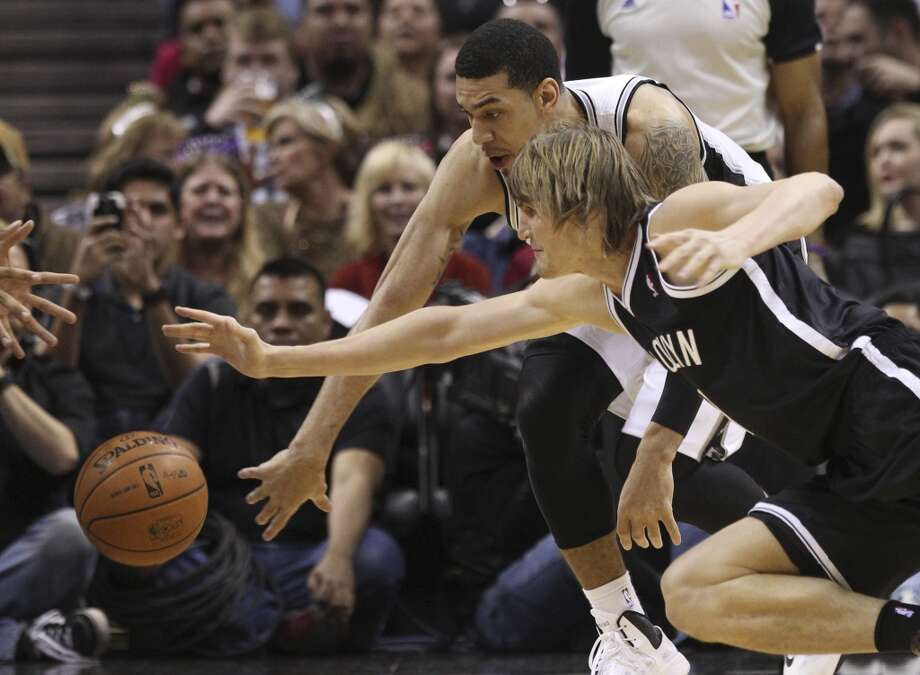 Spurs' Danny Green (04) and Brooklyn Nets' Andrei Kirilenko (47) compete for a loose ball in the first half at the AT&T Center on Tuesday, Dec. 31, 2013. (Kin Man Hui/San Antonio Express-News) Photo: San Antonio Express-News