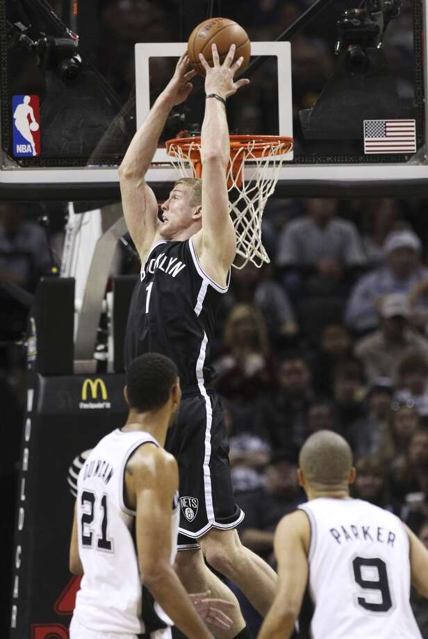 Spurs' Tim Duncan (21) watches Brooklyn Nets' Mason Plumlee (01) go up for an alley-oop dunk in the second half at the AT&T Center on Tuesday, Dec. 31, 2013. Spurs win 113-92. (Kin Man Hui/San Antonio Express-News) Photo: San Antonio Express-News