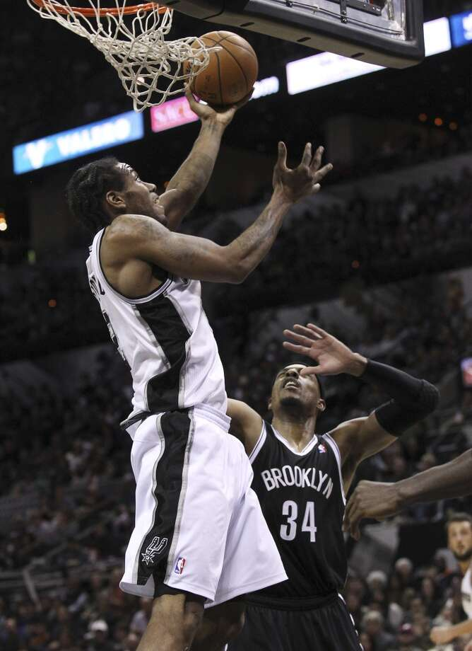 Spurs' Kawhi Leonard (02) attempts a reverse layup against Brooklyn Nets' Paul Pierce (34) in the second half at the AT&T Center on Tuesday, Dec. 31, 2013. Spurs win 113-92. (Kin Man Hui/San Antonio Express-News) Photo: San Antonio Express-News
