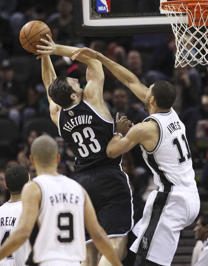Spurs' Jeff Ayres (11) defends a shot against Brooklyn Nets' Mirza Teletovic (33) in the first half at the AT&T Center on Tuesday, Dec. 31, 2013. (Kin Man Hui/San Antonio Express-News) Photo: San Antonio Express-News