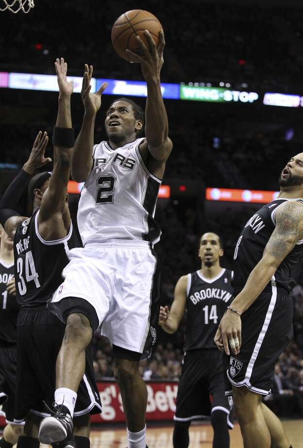 Spurs' Kawhi Leonard (02) drives to the basket against Brooklyn Nets' Paul Pierce (34) and Deron Williams (08) in the first half at the AT&T Center on Tuesday, Dec. 31, 2013. (Kin Man Hui/San Antonio Express-News) Photo: San Antonio Express-News