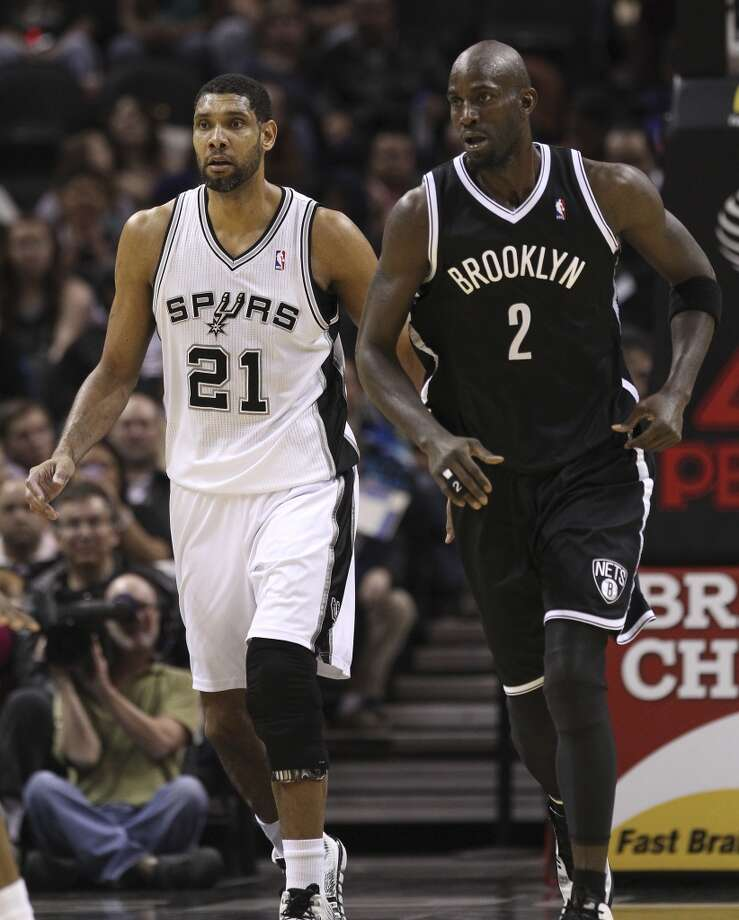 Spurs' Tim Duncan (21) and Brooklyn Nets' Kevin Garnett (02) play against one another in the first half at the AT&T Center on Tuesday, Dec. 31, 2013. (Kin Man Hui/San Antonio Express-News) Photo: San Antonio Express-News