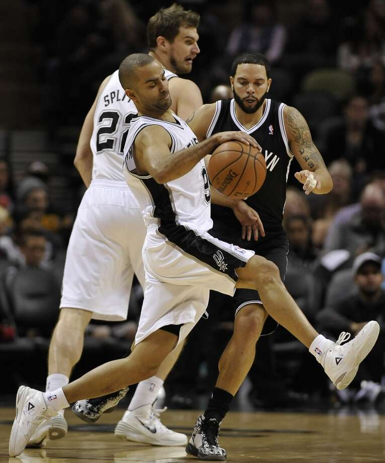 San Antonio Spurs guard Tony Parker, front, of France, recovers after colliding with Brooklyn Nets guard Deron Williams during the first half of an NBA basketball game on Tuesday, Dec. 31, 2013, in San Antonio. (AP Photo/Darren Abate) Photo: Associated Press