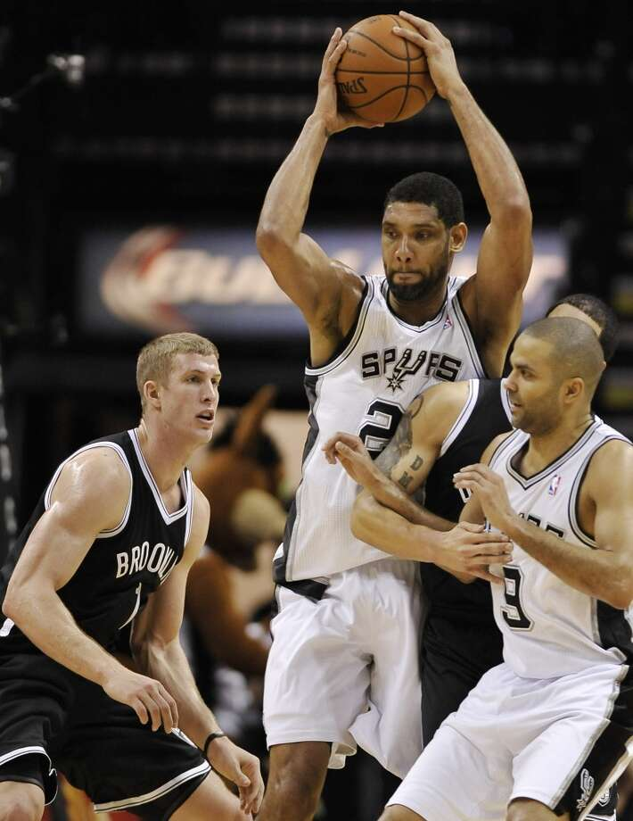 San Antonio Spurs forward Tim Duncan, center, and Spurs guard Tony Parker, right, of France, come away with the rebound against Brooklyn Nets forward Mason Plumlee, left, and Nets guard Deron Williams, during the second half of an NBA basketball game on Tuesday, Dec. 31, 2013, in San Antonio. San Antonio won 113-92.(AP Photo/Darren Abate) Photo: Associated Press