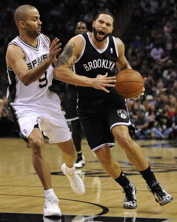 Brooklyn Nets guard Deron Williams, right, drives around San Antonio Spurs guard Tony Parker, of France, during the first half of an NBA basketball game on Tuesday, Dec. 31, 2013, in San Antonio. (AP Photo/Darren Abate) Photo: Associated Press