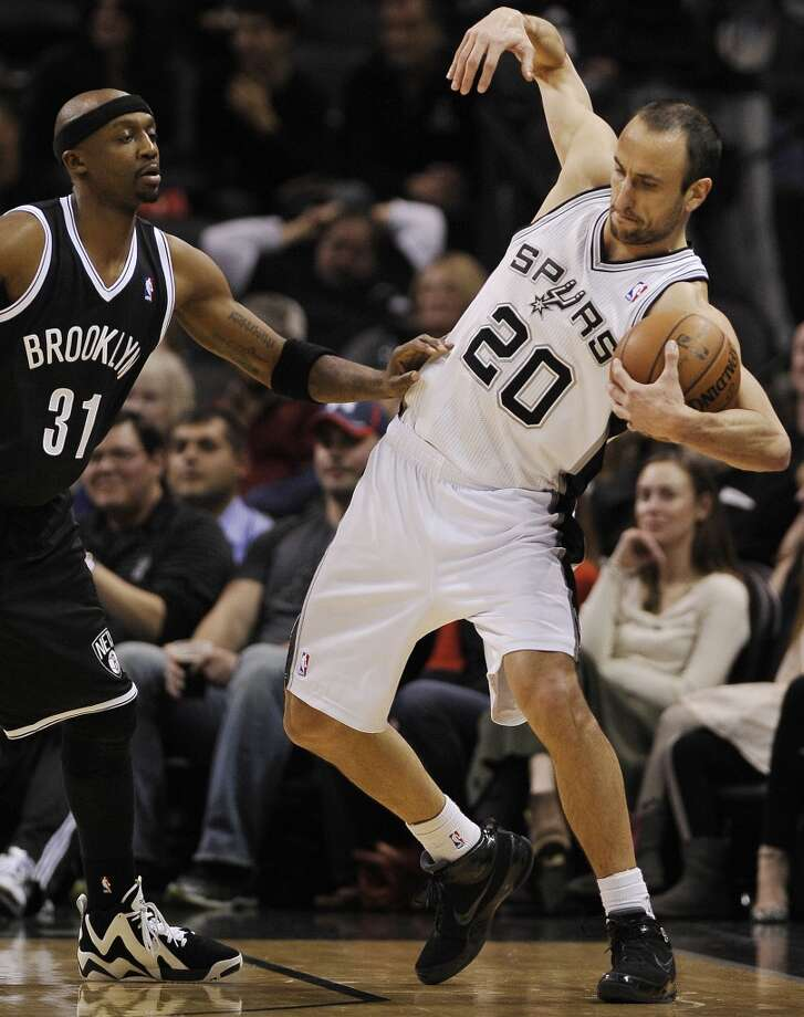 San Antonio Spurs guard Manu Ginobili, right, of Argentina, recovers after tangling with Brooklyn Nets guard Jason Terry during the second half of an NBA basketball game on Tuesday, Dec. 31, 2013, in San Antonio. San Antonio won 113-92.(AP Photo/Darren Abate) Photo: Associated Press